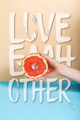 cropped view of female hand with juicy grapefruit half near love each other lettering on beige and blue