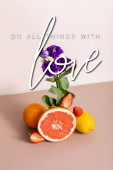 floral and fruit composition with purple eustoma and summer fruits near do all things with love lettering on beige