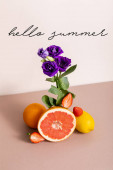 floral and fruit composition with purple eustoma and summer fruits near hello summer lettering on beige