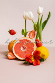 floral and fruit composition with tulips, red Alstroemeria, summer fruits near hello summer lettering on beige