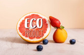 fruit composition with berries, grapefruit and apricot near eco product lettering on beige