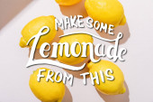 top view of whole fresh lemons on grey table with make some lemonade from this lettering