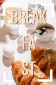 Vařená vejce, dva croissanty, šálek kávy a sklenice vody s citrónem na šedém stole se snídaní