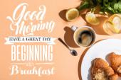 Draufsicht auf Kaffee und Croissants zum Frühstück auf beigem Tisch mit Guten Morgen, guten Tag, beginnend mit dem Frühstücksaufdruck