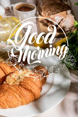 Fresh croissants, bread, coffee and lemon water on grey table, selective focus with healthy breakfast, good morning lettering stock vector
