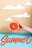 cropped view of woman holding juicy half of grapefruit near summer lettering on beige and blue