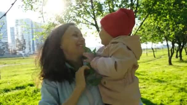 Šťastná rodina hraje s pobočkou v parku při západu slunce. Matka drží dítě v náručí venku