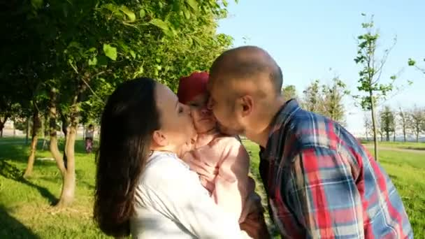 Rodiče dítě políbit na obou tvářích. Mladá rodina s odpočinek o přírodě v parku při západu slunce