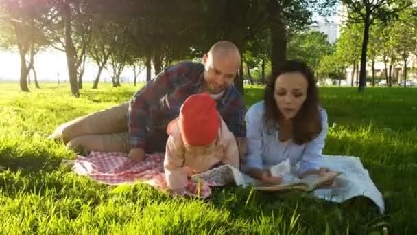 Šťastná rodina leží na trávě a číst knihu na piknik s dítětem při západu slunce v parku