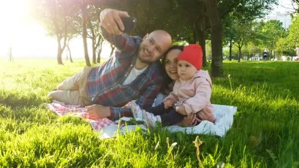 Šťastná rodina je pokládka na trávě a dělají selfie s dítětem při západu slunce v parku. Otec a matka fotit sebe sama s dítětem na telefonu