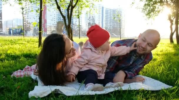 Šťastná rodina leží na trávě v letním parku. Rodiče políbit malou holčičku na tvářích na obou stranách