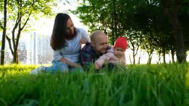 glückliche Familie ruht sich auf der Natur aus. Eltern spielen im Sommer bei Sonnenuntergang mit einer kleinen Tochter in einem Park, Kamerafahrt