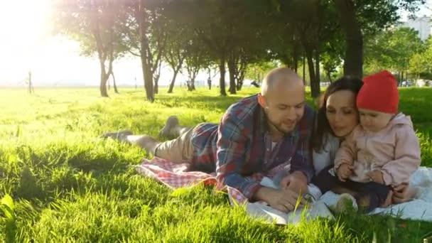 Šťastná rodina oddechuje a líbání v přírodě s dítětem při západu slunce v parku. Otec matku polibky