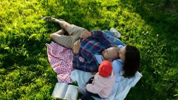 Šťastná rodina je pokládka na doznal a dělají selfie s dítětem při západu slunce v parku. Otec a matka fotit sebe sama s dítětem, pohyb kamery