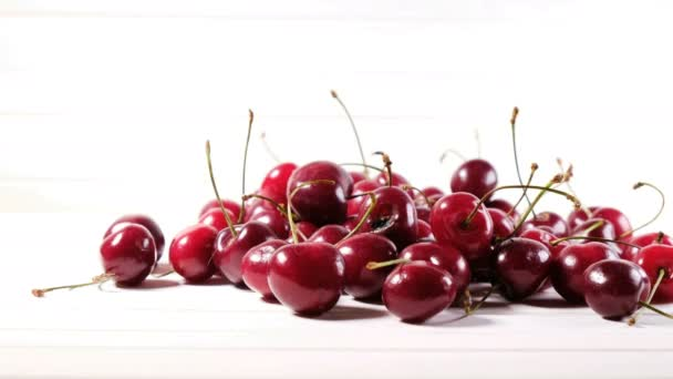 Girl lays berries from a plate on a white background, ripe cherries lie on a table