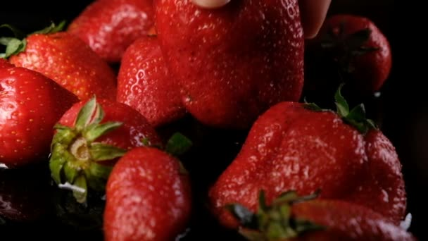Woman puts a ripe juicy big strawberry berry into the water on a dark background, close-up