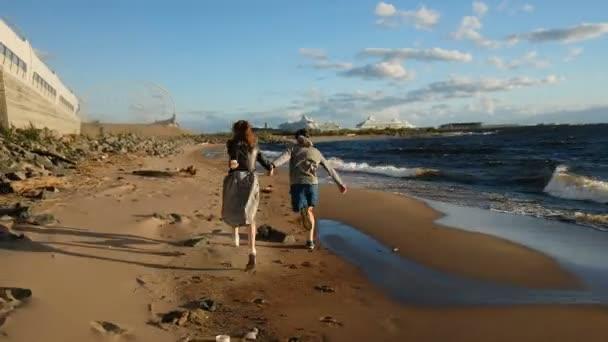 Liebespaar rennt bei Sonnenuntergang ans Meer. europäisches Paar spielt am Strand miteinander