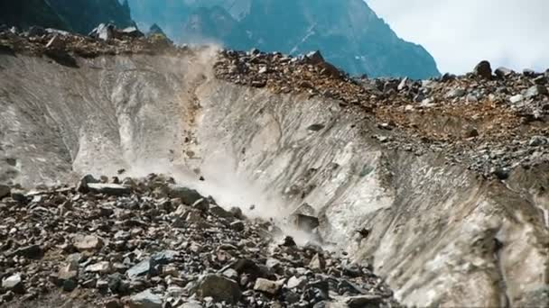 Slow motion rockfall in the mountains close up. People run away from falling rocks in the mountains, crash and fear. Instinct of self-preservation in an emergency situation