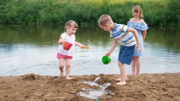 Kleine Kinder spielen im Sommer im Fluss, ein Mädchen und ein Junge bauen einen Bach. Mutter kümmert sich beim Spaziergang um Babys