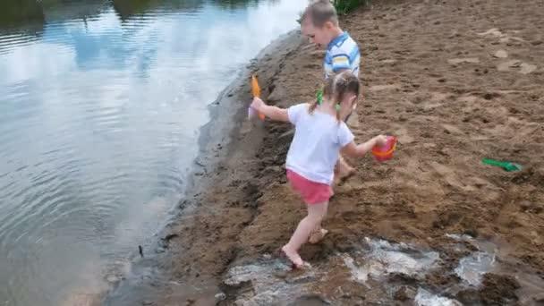 Kleine Kinder spielen im Sand am Fluss. Kinder bauen mit Eimern und Schaufel einen Bach