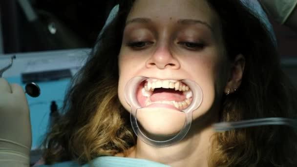 Frau behandelt Zähne mit einem kieferorthopädischen Fixator im Mund aus nächster Nähe. Zahnarztbesuch