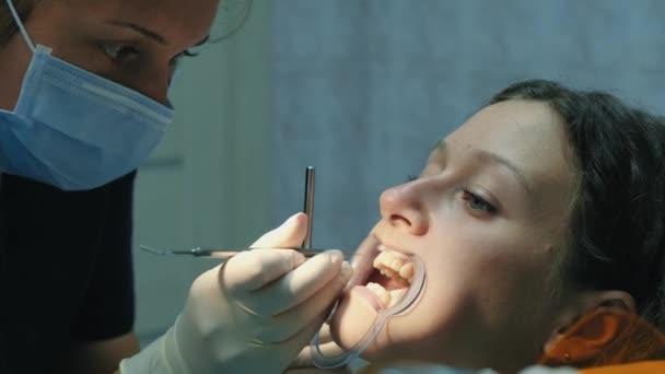 Besuch beim Zahnarzt, Installation von das Bracket-System. Kieferorthopäden korrigiert die Set Halterung und sieht in der Mundspiegel-Nahaufnahme