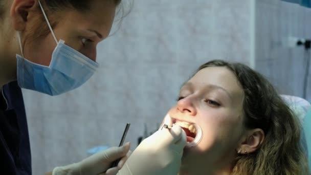 Návštěva zubaře. Ortodontista lékař nastaví železné výztuhy pro ženu s zubní fixátor