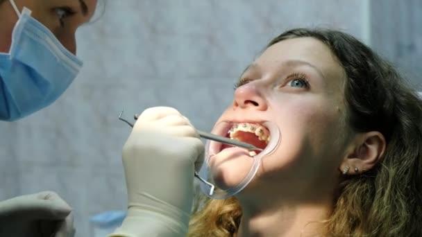 Montage und Befestigung des Metallbügelsystems. Zahnarztbesuch, Kieferorthopädie, Korrektur von Fehlverschlüssen