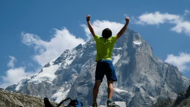 Muž zdvihne ruku v horách v výlet stojí na kámen, se otevírá krásný výhled. Koncept vítězství a úspěch, dosažení cíle, pomalý pohyb