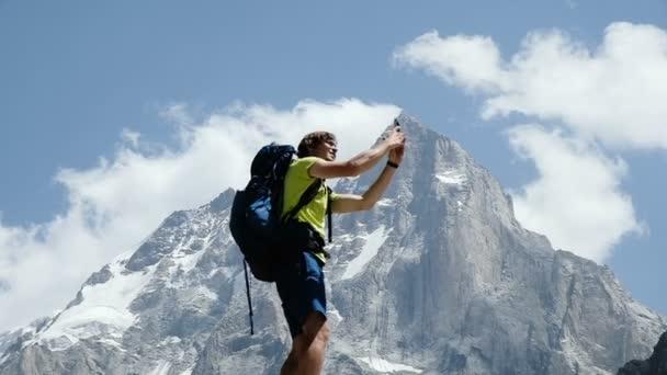 Bergsteiger Mann mit Rucksack macht ein Selfie auf einem Smartphone mit anderen Emotionen. Erfolgskonzept, Erreichen des Ziels und des Sieges, Zeitlupe