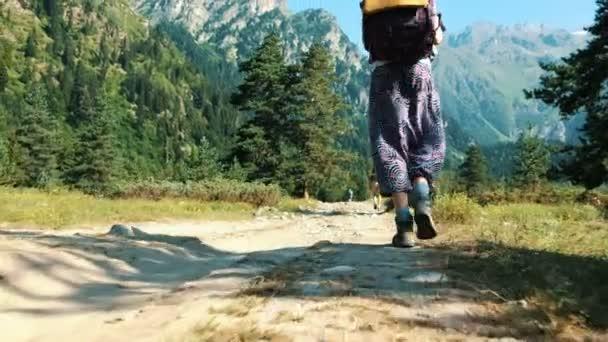 Nohy ženy v trekingové boty, batoh jdou na výlet na pozadí krásné horské krajiny