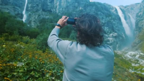 Man hiker traveler tourist photographs high waterfalls in the mountains on a smartphone close-up