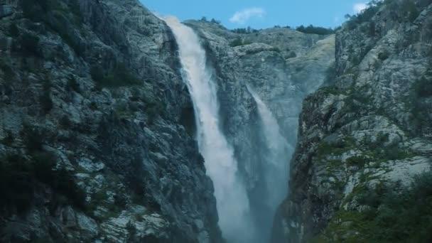 Obrovský vodopád v horách, silný proud vody padá ze skály, pomalý pohyb