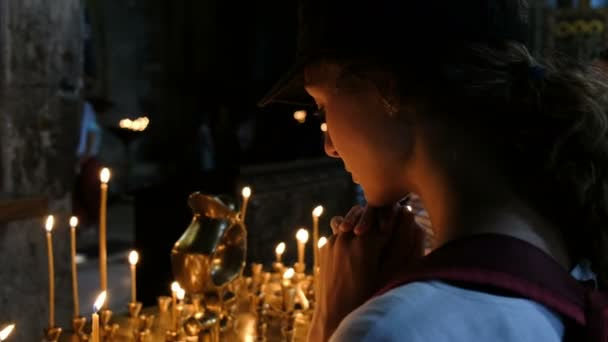 Woman tourist recites a prayer in an Orthodox Catholic ancient church