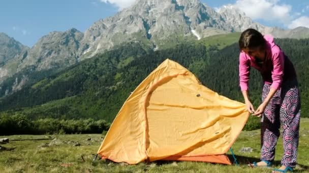Happy tourist girl sets up tent in the mountains for relaxing