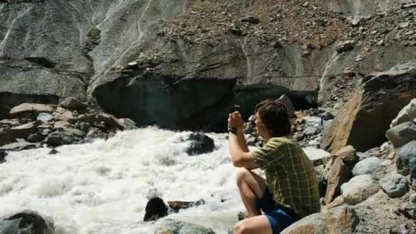 Man photographs on a smartphone landscape - mountain river, a glacier