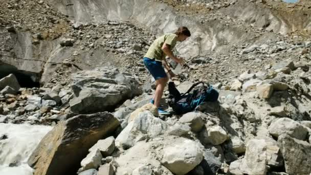 Tourist puts on a hiking backpack and goes on a mountain climbing route