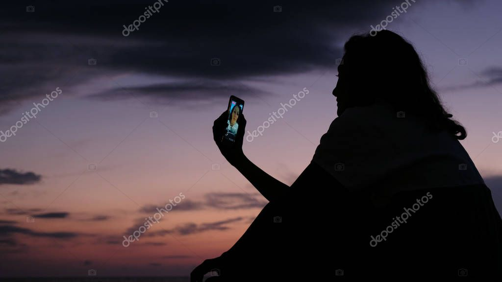 Silhouette of a girl uses a smartphone to live on social networks at sunset