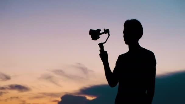 Egy turista férfi egy videó kamerát és egy stabilizáló sziluettek közelről