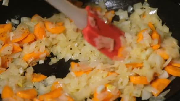 Cook se mísí, smažené cibule a mrkev v pánvi detail