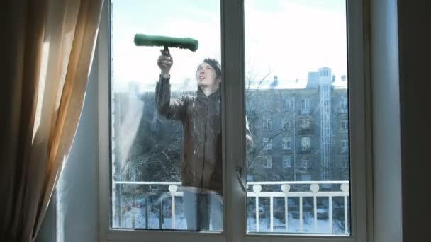 Muž lathers špinavá okna sám doma na balkoně