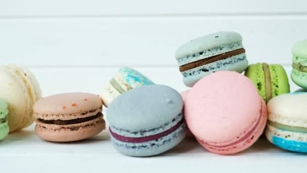 Makronky nebo macarons leží na bílé dřevěné pozadí řádku mandlové sušenky