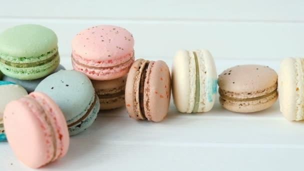 Vícebarevné makronky nebo macarons leží na bílé dřevěné pozadí řádku mandlové sušenky