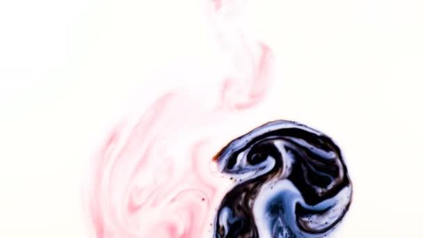 Červená a černá psychedelické barvy jsou smíchány do abstraktní vzory v bílé mléko