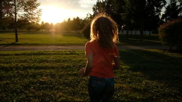 Super slow motion - una donna è jogging sullerba sullo sfondo della luce solare