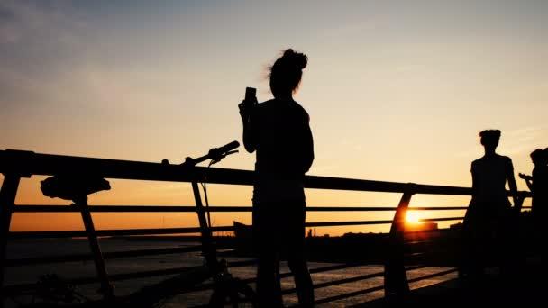 Mädchen fotografiert Sonnenuntergang mit Handykamera