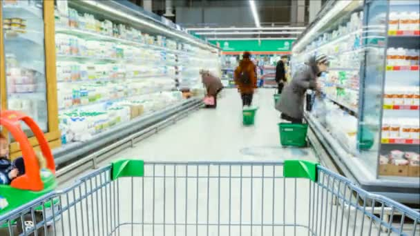 Timelapse - shopping trolley stands on the background of blurred customers in the aisle, people choose products