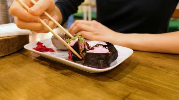 Lány egy vegetáriánus kávézóban eszik nyers élelmiszer tekercs, zöldség