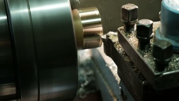 Facing operation of a brass blank on turning machine with cutting tool. Old turning lathe machine in turning workshop. Operator machining high precision mold part by lathe