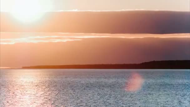 Time-lapse sun sets behind a cloud - a red-pink sunset on the sea or a large lake